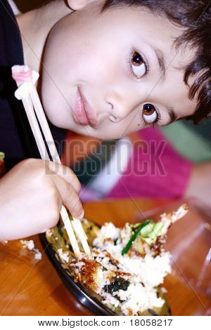 Young boy enjoying some Japanese prawn tempura and fried sushi, trying them with a pair of chopsticks.