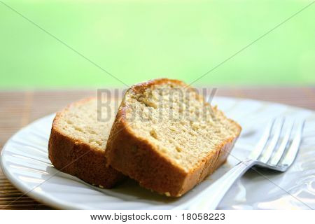 Two slices of banana cake and fork on white plate. Narrow DOF.