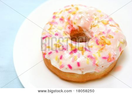 A delicious ring donut with sugar glazing and sprinkling of colorful hundreds of thousands .