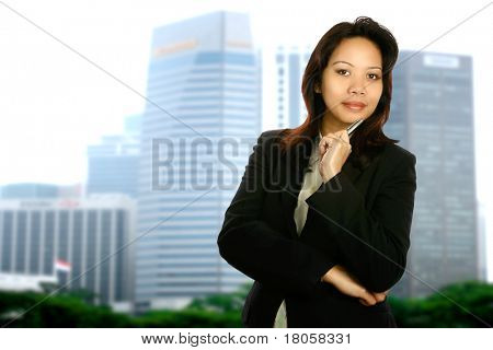 Asian businesswoman standing by an office window with view of cityscape in the background