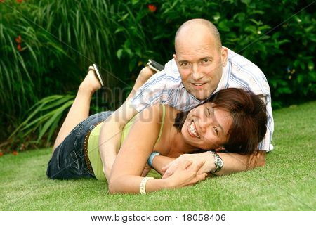 Happy caucasian man and chinese woman playful in the garden.