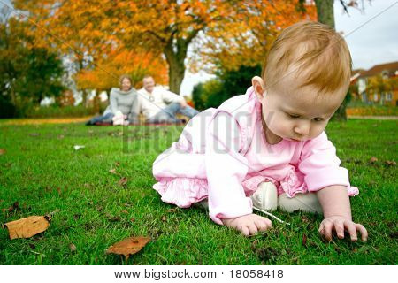 Curious baby girl feeling the texture of grass and mud underneath her fingers as parents look on in the background.