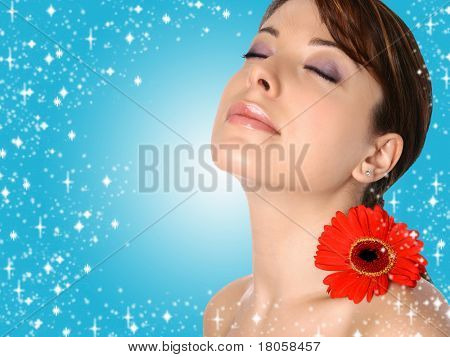 Beautiful young woman in sensual spa setting with red gerbera on blue sparkly background.
