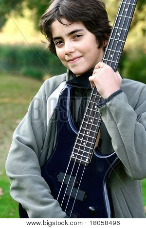 Young boy proudly showing off his accoustic guitar.