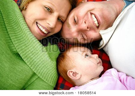 Young family lying on picnic rug , enjoying the outdoors.