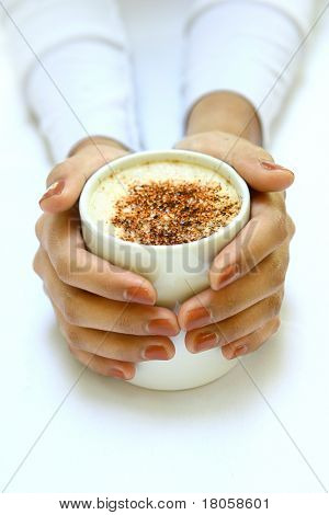Feminine pair of hands gently warming against a cup of frothy coffee with chocolate sprinkles
