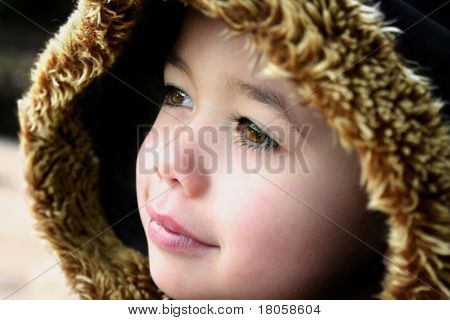 Young boy with fluffy hooded winter coat, feeling the chill in the air, outdoors.