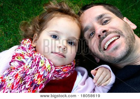 Father and his beautiful little girl having fun lying on the grass.