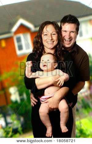 Young family outdoors, with house in background