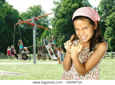 Young girl showing her fist and feeling angry with playground in background