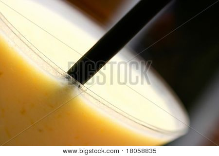 Closeup of blended mango and peach smoothie in cocktail glass with black straw