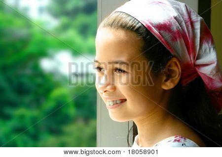 Muy joven en el pañuelo rosa que da a la naturaleza es al aire libre.