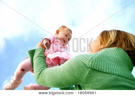 Young mother with her new baby, having fun playing outdoor.