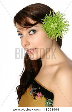 Beautiful young woman in batik wrap with green gerbera in her hair, isolated on white.
