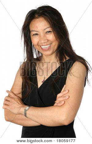 Beautiful mature Thai female in formal black dress appearing happy and cheerful, isolated on white background.