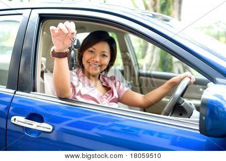 Young Asian feminino mostrando a chave do carro estando no assento do motorista de um carro azul.