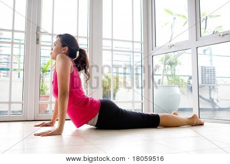 Young Asian female stretching her back to strengthen, in a calm home environment