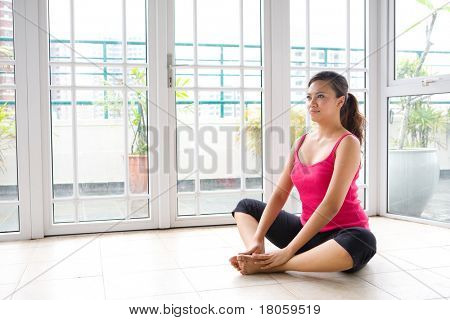 Young Asian female in sitting yoga position, cooling down after an exercise session.