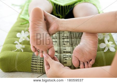 Lady masseur giving female patient a foot reflexology.