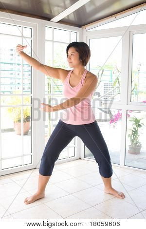 Young Asian female doing tai-chi exercise.