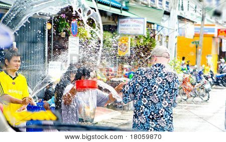 A tourist getting soaked by the local Thai people by roadside ready with buckets of water to be thrown towards passers by in celebrating the Thai SOngkran water festival