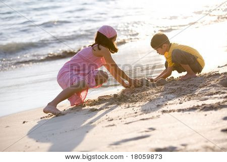 Two young children making sand castle together on a beautiful warm evening by the sea.