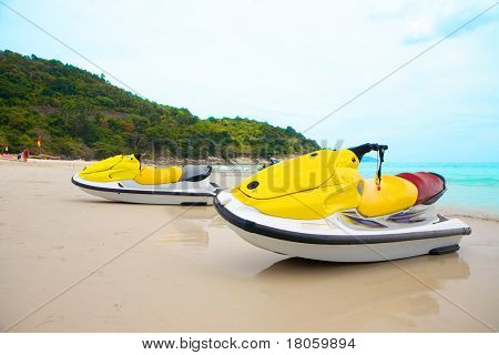 Two jetskis on sandy beach against blue sky and crystal clear water of Phuket, Thailand