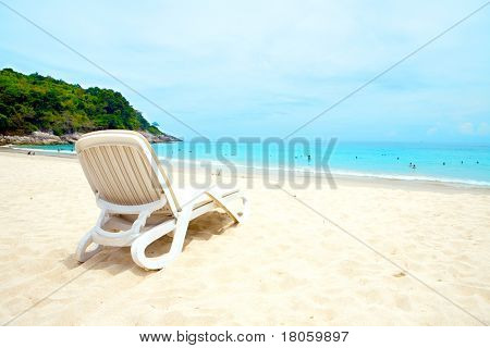 A sun lounger by a sandy beach against crystal blue sea and blue sky of Phuket beach, Thailand