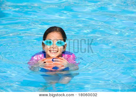 Young girl having fun playing with rubber ball in swimming pool.
