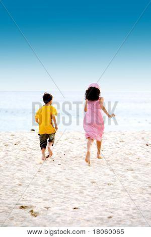 Emocionado hermano y hermana en la playa de arena suave hacia el mar