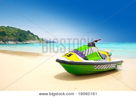 Jetski parked on a beach against blue sky and crystal blue water