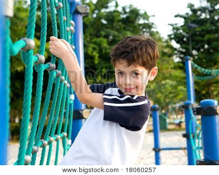 Young boy on climbing rope in playground