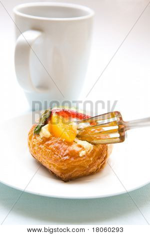 A fork slicing a piece of fruity danish pastry, with cup of hot drink in background