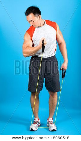 Muscular fitness man using exercise tubing to strengthen upper arm.