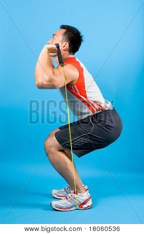 Young fitness man using elastic exercise tubing to strengthen upper arm and back muscle