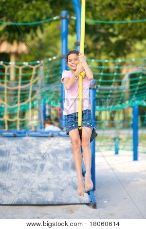 Young girl dangling on playground swing