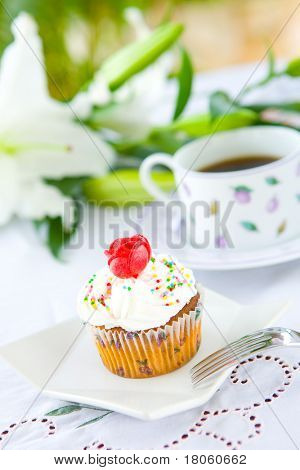 Single pretty cupcake with butter icing and red rose biscuit served with cup of black coffee