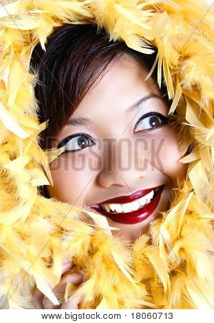 Pretty young woman with bright eyes and red lips with feather boa smiling happily.