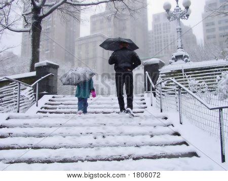 Pequeñita y hombre en nieve en Nueva York