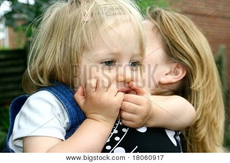 Toddler girl on her mother's shoulder, playing outdoor