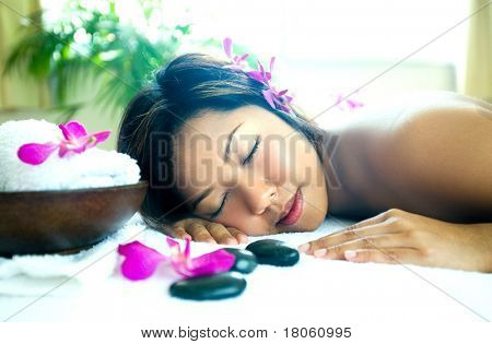 Young woman resting as she enjoys a body therapy session at spa