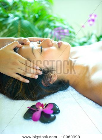 Young woman enjoying a holistic head massage in tropical spa.