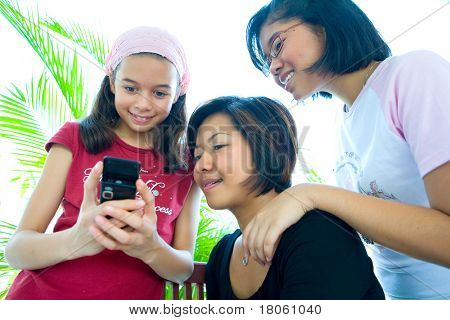 Three young girls of different ages looking at a cell phone.