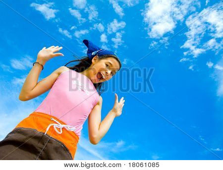 Young girl in swimming costume cheerful and happy with beautiful blue sky in  the background
