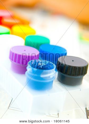 Row of colorful poster paint pots