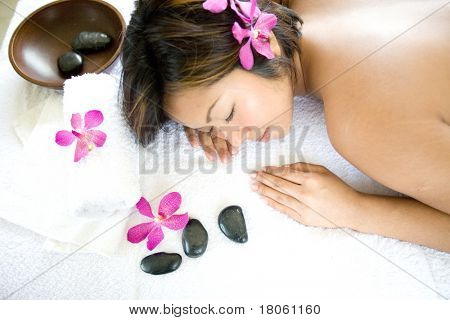 Young Asian woman restful on massage therapy bed in spa