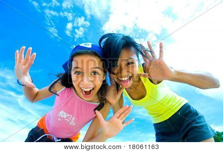 Two young girls having fun making funny faces with beautiful sky background