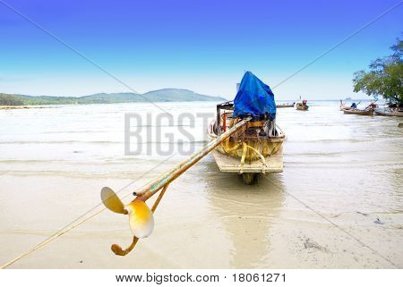 A long tail boat by the beach awaits high tide at Krabi bay, Thailand