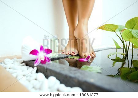 Pair of feminine feet by a sunken foot bath with foot lotion and soap on side