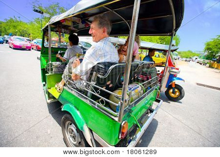 Senior with grandaughter enjoying a fast ride on Bangkok's most popular method of transportation,the '' tuktuk '', Bangkok Thailand
